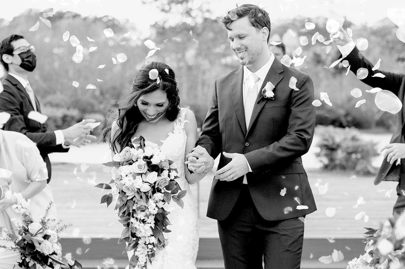 Wedding Photographer in Houston - Newlyweds smiling down the aisle