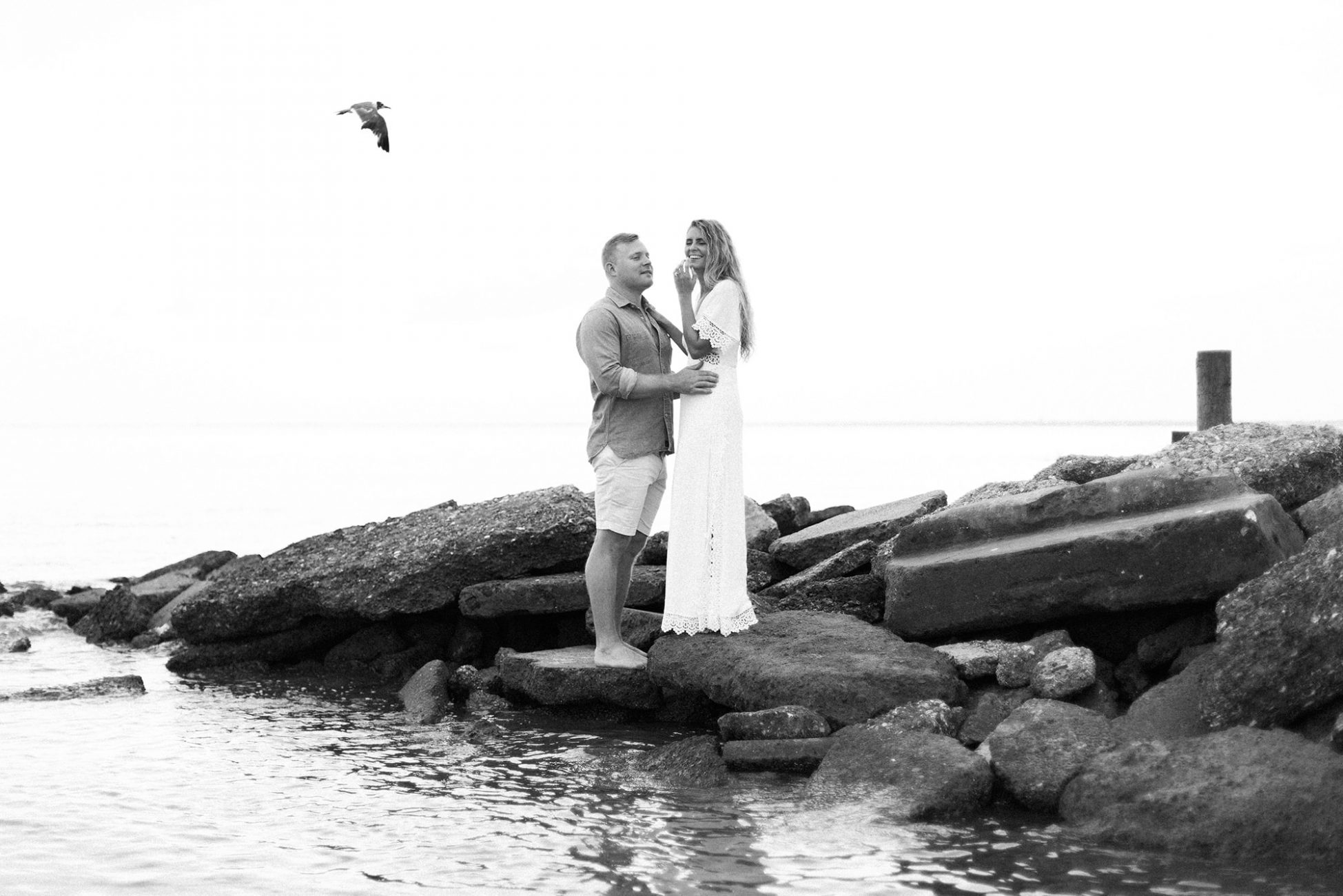 Newlywed couple laughing on beach rock formation